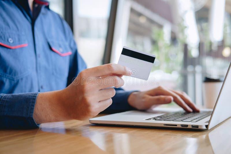 L'uomo d'affari che tiene la carta di credito e che scrive sul computer portatile per acquisto ed il pagamento online fa un acqui immagine stock