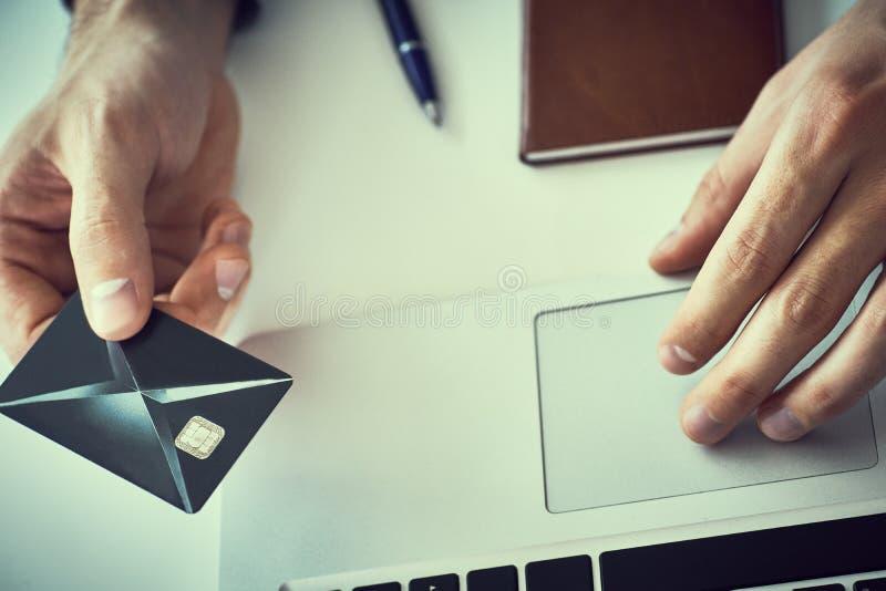 L'uomo d'affari che tiene la carta di credito e che scrive sul computer portatile per acquisto ed il pagamento online fa un acqui fotografie stock libere da diritti