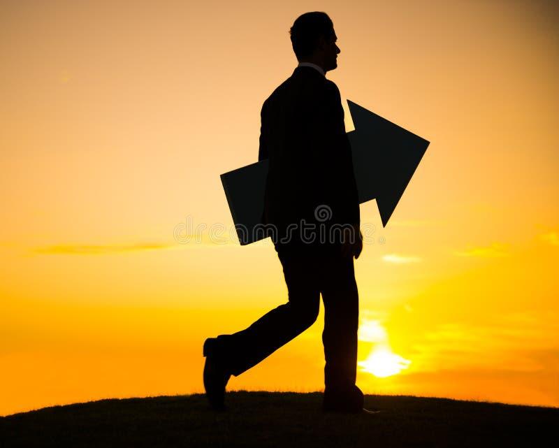 L'uomo d'affari che tiene la freccia e continua camminare immagini stock libere da diritti