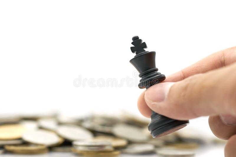 L'uomo d'affari che tiene un re Chess è disposto su un mucchio delle monete usando come il concetto di affari del fondo e concett immagini stock