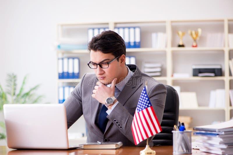 L'uomo d'affari con la bandiera americana in ufficio immagini stock libere da diritti