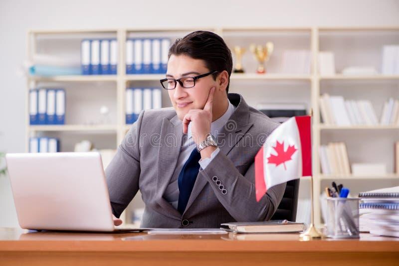 L'uomo d'affari con la bandiera canadese in ufficio fotografia stock
