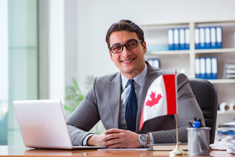 L'uomo d'affari con la bandiera canadese in ufficio immagine stock