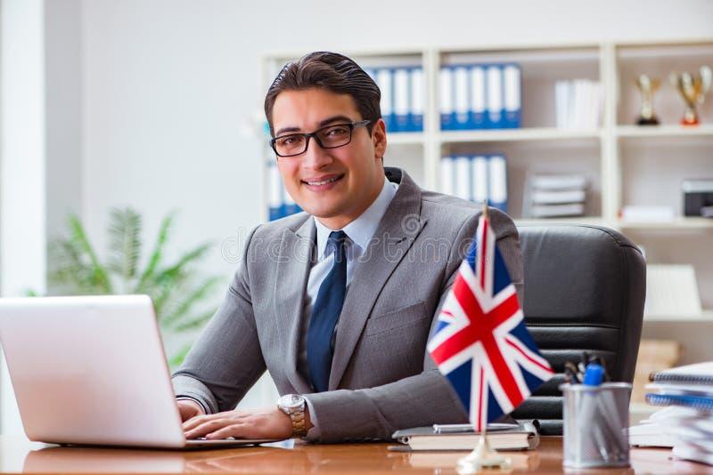 L'uomo d'affari con la bandiera di britannici nell'ufficio immagine stock