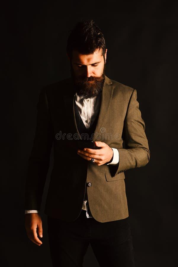 L'uomo d'affari con la barba tiene il telefono cellulare Uomo in vestito astuto fotografie stock libere da diritti