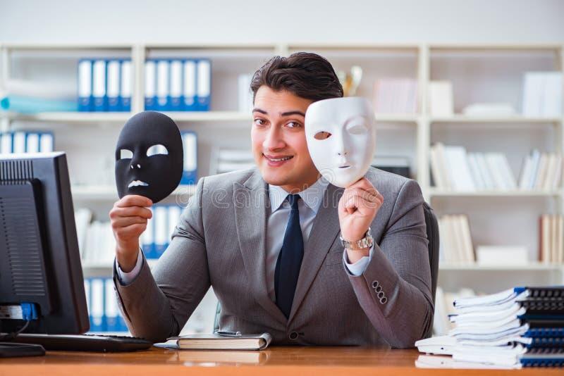 L'uomo d'affari con la maschera nel concetto di ipocrisia dell'ufficio fotografia stock