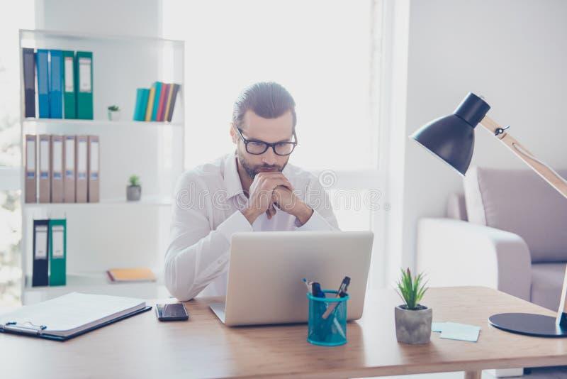 L'uomo d'affari concentrato alla moda in camicia bianca lavora in ufficio immagini stock