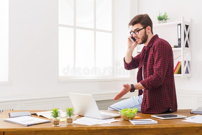 L'uomo d'affari concentrato giovani ha letto i documenti in ufficio bianco moderno fotografia stock