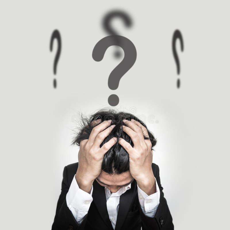 L'uomo d'affari confuso con i punti interrogativi firma sulla testa fotografia stock