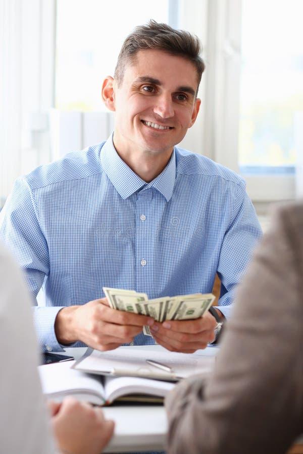 L'uomo d'affari considera i dollari dei contanti nell'ufficio fotografia stock libera da diritti