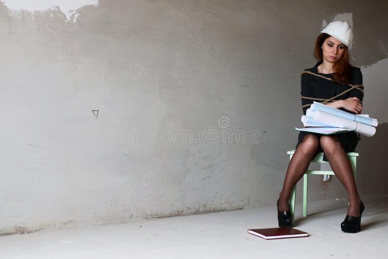L'uomo d'affari della donna che si siede sulla sedia ha associato il concetto di stakanovista fotografia stock