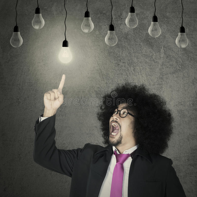 L'uomo d'affari di afro sceglie la lampadina immagini stock libere da diritti