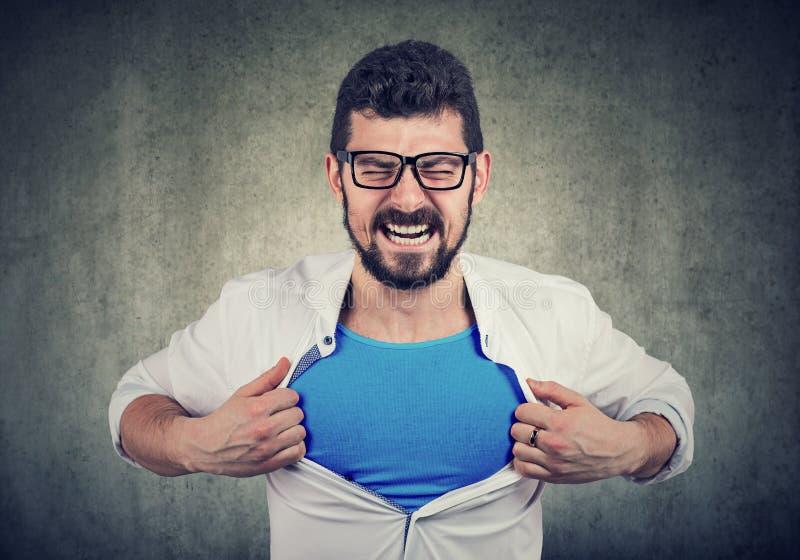 L'uomo d'affari disperato per cambiamento sbottona la sua camicia e diventare un superman immagini stock