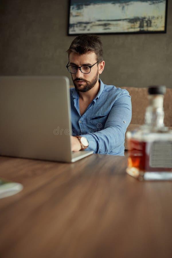 L'uomo d'affari domestico lavorante del ¬â€œ del 'di ââ di concetto lavora per un computer da una casa con un computer portatile immagini stock
