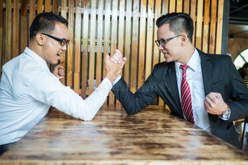 L'uomo d'affari due ha espresso un'espressione e un combattimento seri dal braccio di ferro usato sulla tavola di legno immagini stock libere da diritti