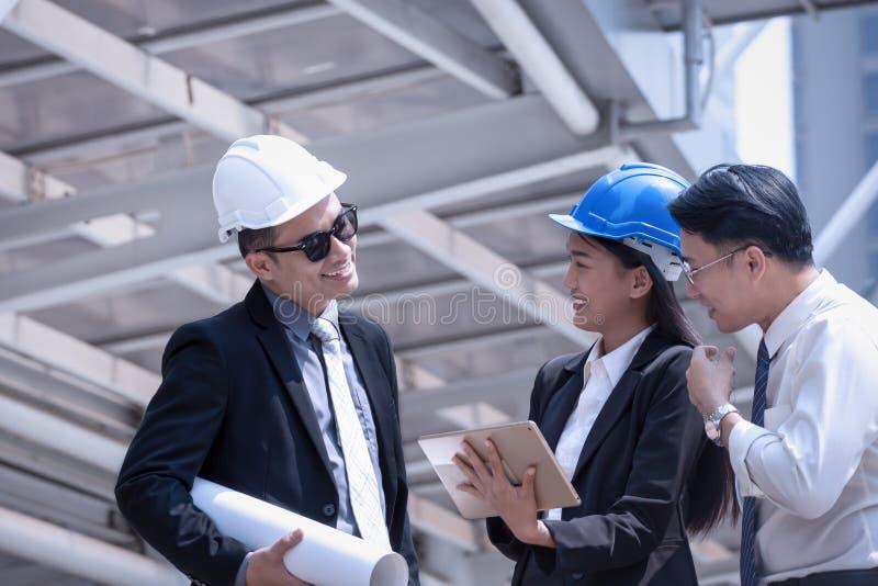 L'uomo d'affari e la donna asiatici discutono con prof. dell'architetto dell'ingegnere immagini stock
