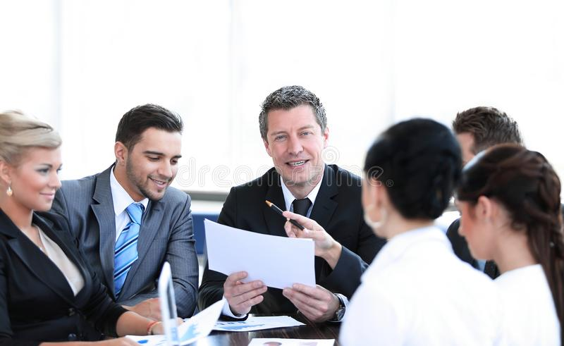 L'uomo d'affari ed il suo affare team discutendo i documenti di lavoro fotografia stock libera da diritti