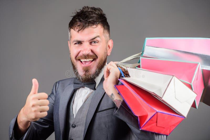 L'uomo d'affari elegante barbuto dell'uomo porta i sacchetti della spesa su fondo grigio Renda comperando più allegro Goda di di  fotografie stock libere da diritti