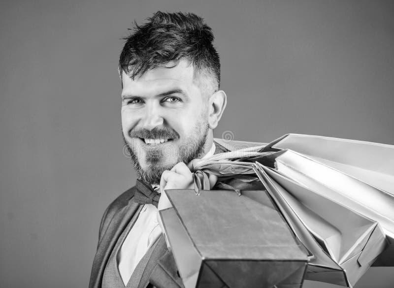 L'uomo d'affari elegante barbuto dell'uomo porta i sacchetti della spesa su fondo grigio Renda comperando pi? allegro Boutique de fotografia stock libera da diritti