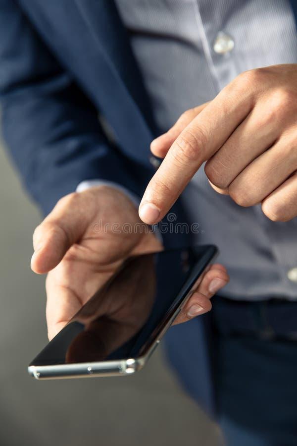 L'uomo d'affari elegante utilizza lo smartphone fotografia stock libera da diritti
