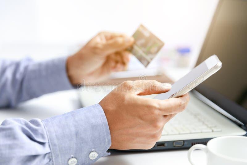 L'uomo d'affari fa la spesa online con la carta di credito ed il telefono cellulare fotografia stock