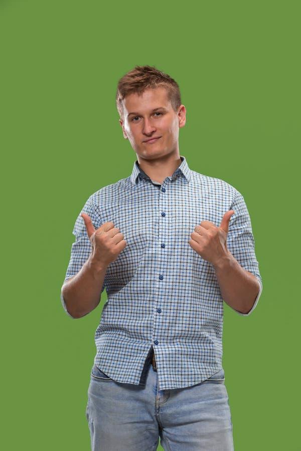L'uomo d'affari felice che sta e che sorride contro il fondo verde fotografia stock