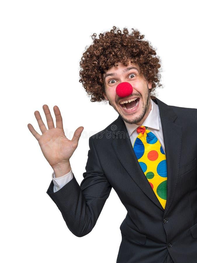 L'uomo d'affari felice in costume del pagliaccio e del vestito sta ondeggiando con la mano Isolato su priorità bassa bianca immagine stock