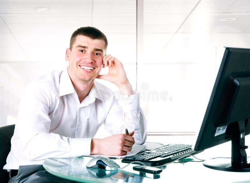 L'uomo d'affari felice si siede al calcolatore immagini stock