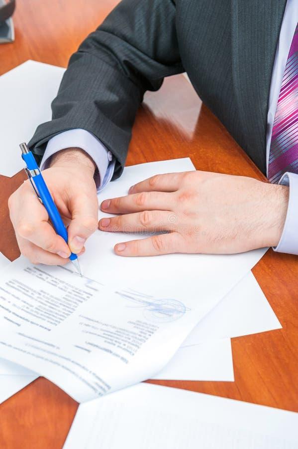 L'uomo d'affari firma i documenti fotografie stock libere da diritti
