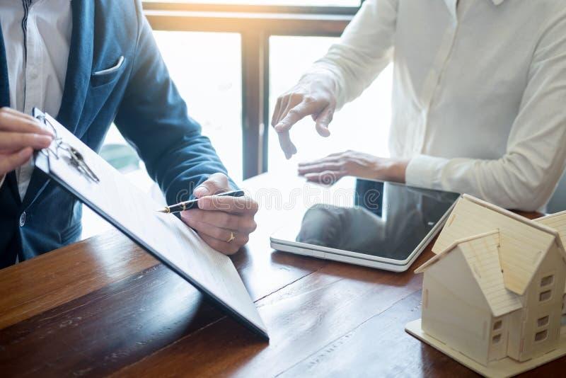 L'uomo d'affari firma il contratto dietro il modelDiscu architettonico domestico fotografia stock libera da diritti