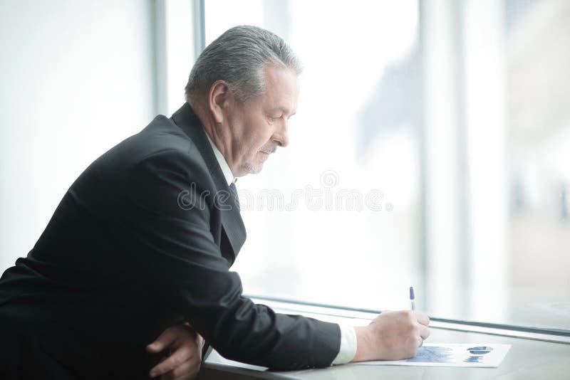 L'uomo d'affari firma un documento, stante vicino alla finestra dell'ufficio immagine stock