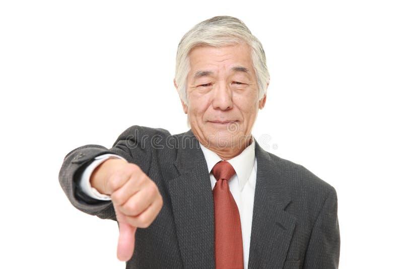 L'uomo d'affari giapponese senior con i pollici giù gesture immagini stock