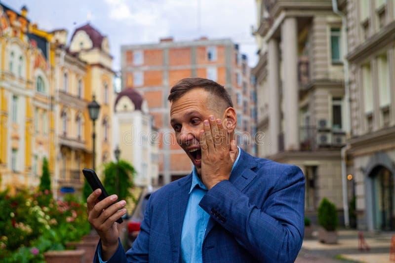 L'uomo d'affari guarda in telefono prove una scossa e una sorpresa fotografia stock