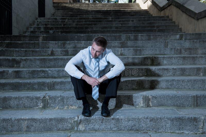 L'uomo d'affari ha diminuito e perso la seduta fuori dopo la perdita del suo lavoro fotografia stock libera da diritti