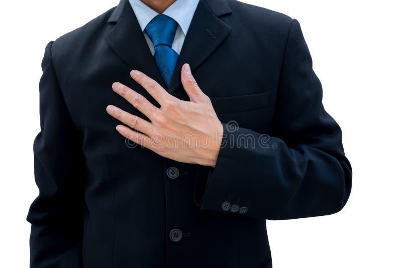 L'uomo d'affari ha messo la sua mano sul suo petto fotografie stock libere da diritti