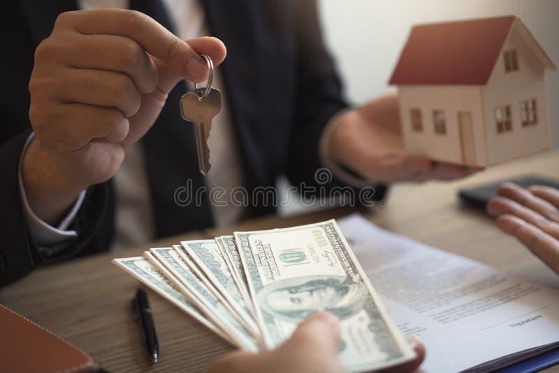 L'uomo d'affari ha passato il modello della casa ed il nuovo proprietario di abitazione che danno i soldi al commercio del bene i immagine stock libera da diritti