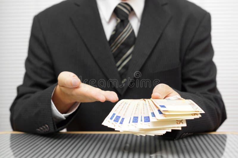 L'uomo d'affari indica che prendete i soldi ed accettate l'affare finan immagine stock