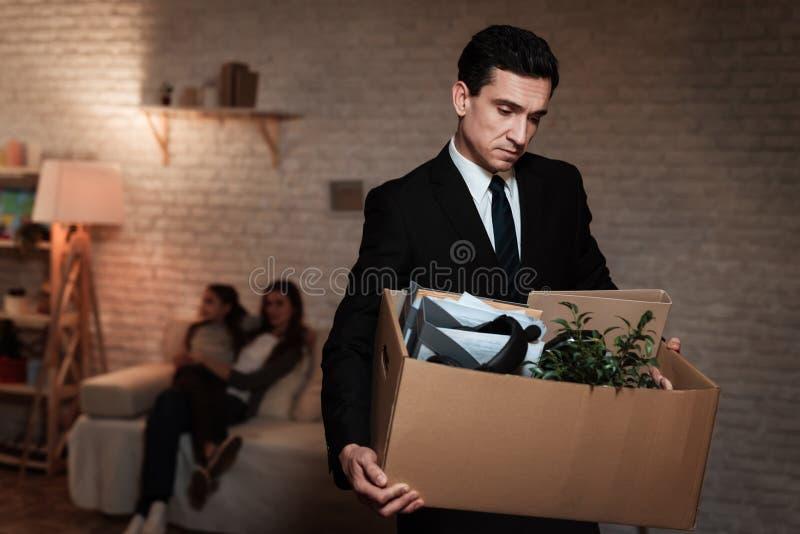 L'uomo d'affari lascia la casa con il contenitore di roba Il padre va via di casa a causa dei problemi in famiglia immagini stock