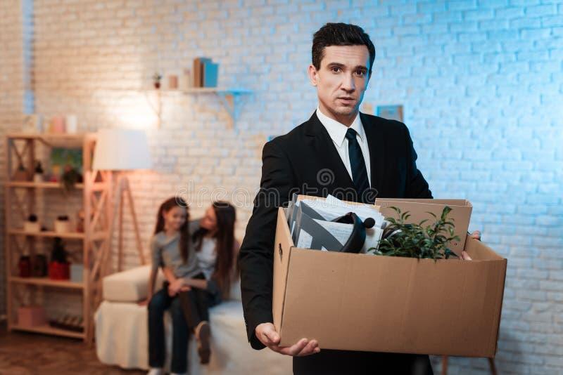 L'uomo d'affari lascia la casa con il contenitore di roba Il padre va via di casa a causa dei problemi in famiglia fotografie stock