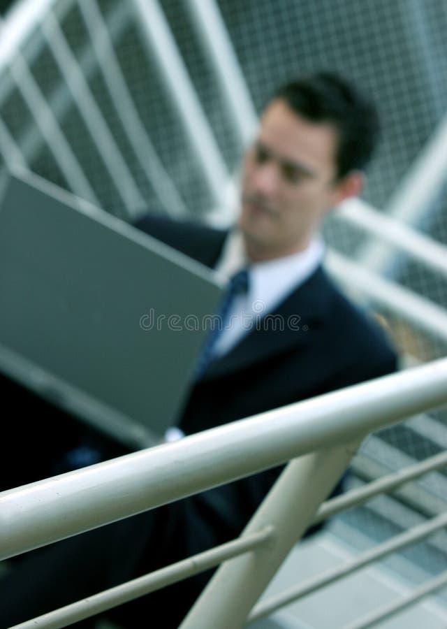 L'uomo d'affari lavora al computer portatile fotografia stock libera da diritti