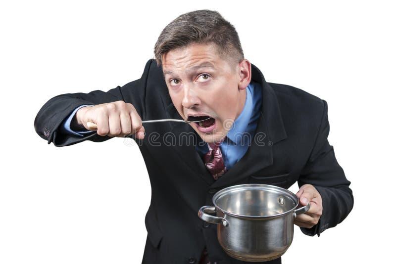 L'uomo d'affari mangia da una pentola fotografia stock