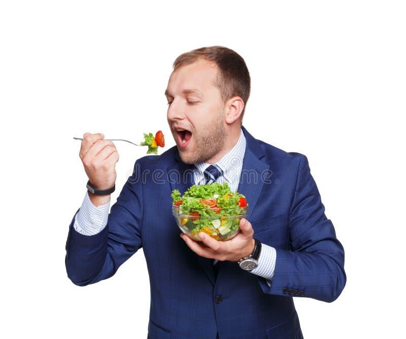 L'uomo d'affari mangia l'insalata della verdura fresca isolata su bianco fotografia stock libera da diritti