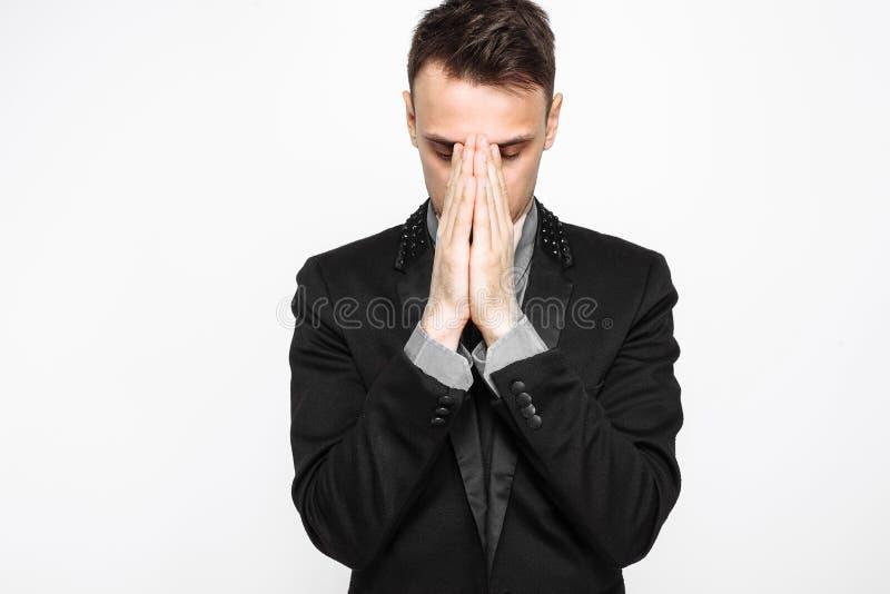 L'uomo d'affari messo a fuoco, in vestito nero, tenentesi per mano insieme, prega fotografie stock libere da diritti