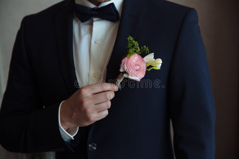 Abbigliamento Ufficio Uomo : L uomo d affari mette sopra un boutonniere su un rivestimento il