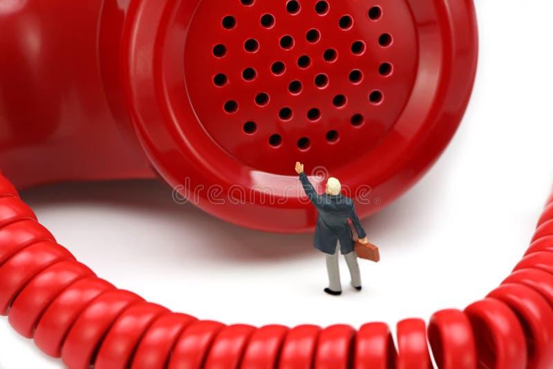 L'uomo d'affari miniatura si leva in piedi davanti ad un telefono fotografia stock libera da diritti