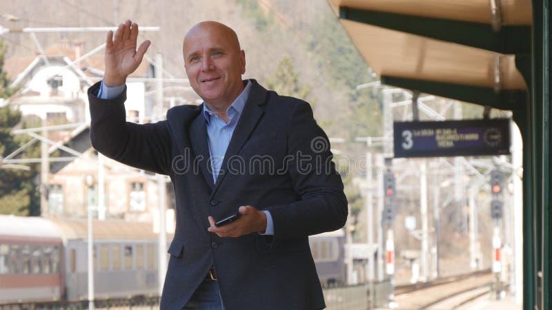 L'uomo d'affari With Mobile Phone a disposizione in una stazione ferroviaria fa ciao i gesti fotografia stock libera da diritti
