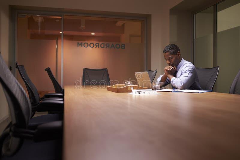 L'uomo d'affari nero invecchiato mezzo lavora tardi al computer portatile in ufficio fotografia stock