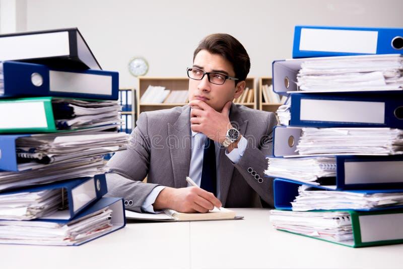 L'uomo d'affari occupato nell'ambito dello sforzo dovuto eccessivo lavoro fotografia stock