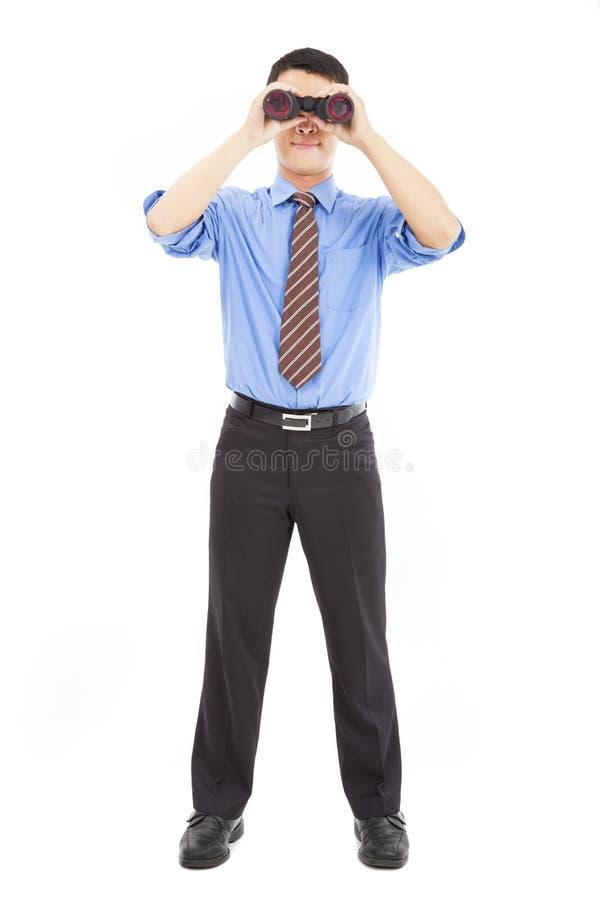L'uomo d'affari osserva tramite il binocolo fotografia stock
