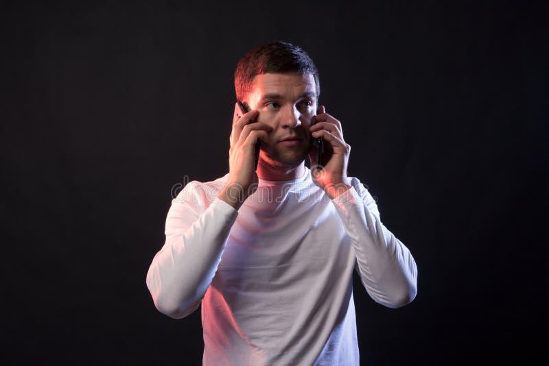 L'uomo d'affari parla su due telefoni e grida da strapazzo e fotografia stock libera da diritti